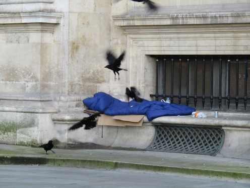 A homeless person's sleeping space, covered in crows - within the Louvre.