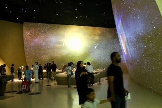 Projectors camouflaged on the ceiling show images of space on the curved walls