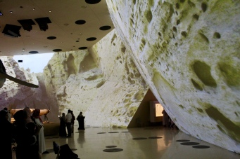 Projectors show different stages of the desert ecosystem on the curved walls
