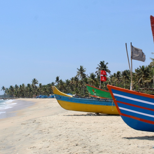 At the other end of the beach are brightly colored fishing boats.