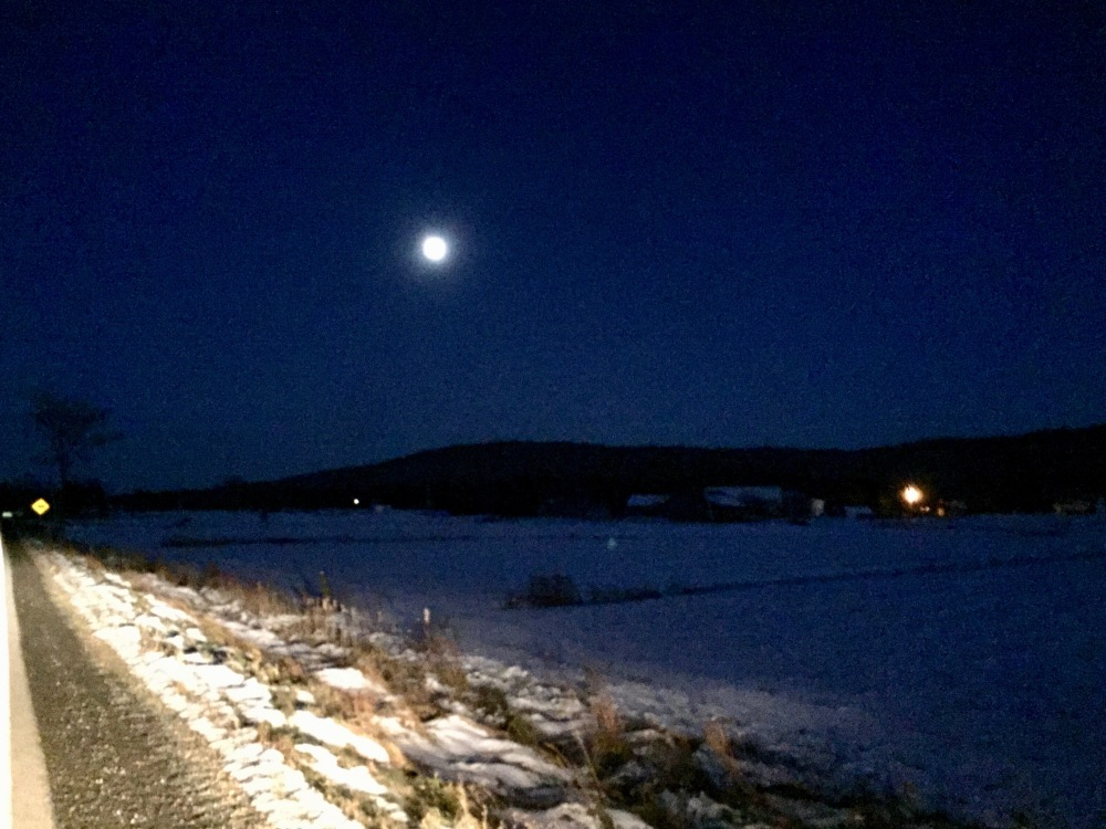 2019 - Windsor, Nova Scotia - An almost full moon shines down on the snow that lightly dusts the farm lands