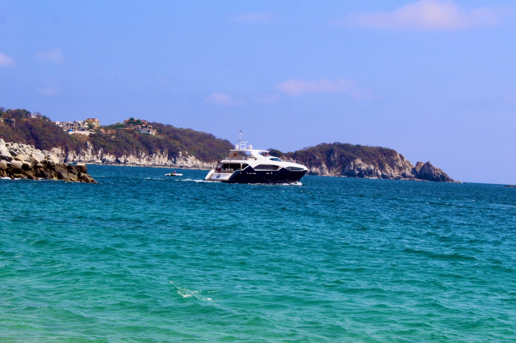2019 - Chahué Bay, Chahue Beach, Huatulco, Mexico - A yacht heads out from the nearby marina