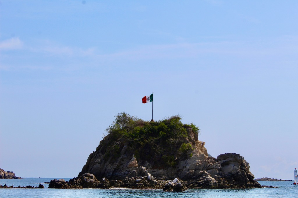 2019 - December - Tangolunda Beach, Huatulco, Mexico - Mexican flag on a small island off the beach